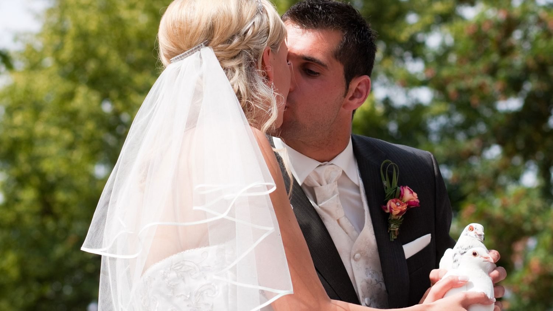 pareja de novios besándose con palomas en la mano